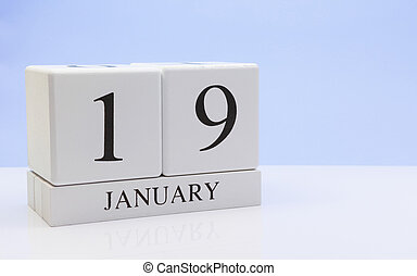January 19st. Day 19 of month, daily calendar on white table with reflection, with light blue background. Winter time, empty space for text