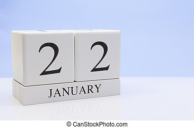 January 22st. Day 22 of month, daily calendar on white table with reflection, with light blue background. Winter time, empty space for text