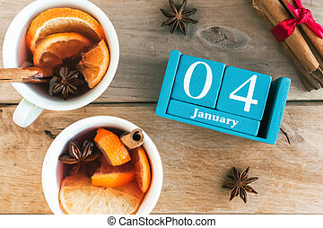 January 4. Blue cube calendar with month and date and cups with mulled wine, wooden background.