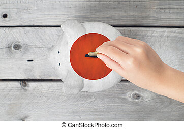 Japan saving concept with little hand dropping a coin into piggy