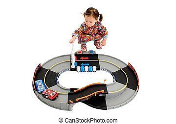 Adorable Japanese American three year old girl playing with electric race car set.