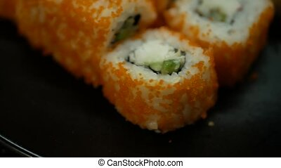Japanese appetizing sushi and rolls, california and tempura on the plate.