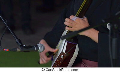 Japanese artist playing on traditional shamisen instrument