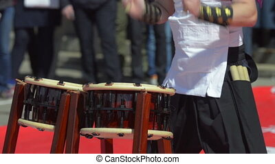 Japanese artist playing on traditional taiko drums