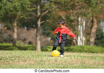 Japanese boy kicking a yellow ball