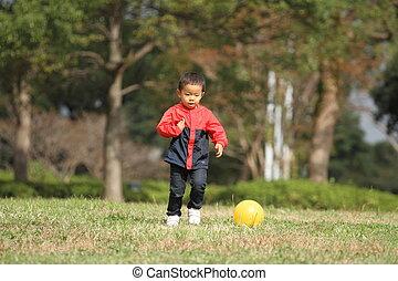 Japanese boy kicking a yellow ball