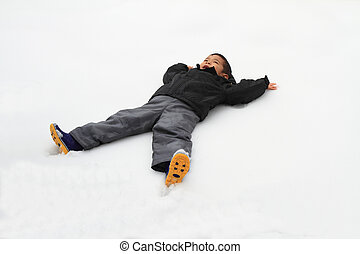 Japanese boy lying on the snow field