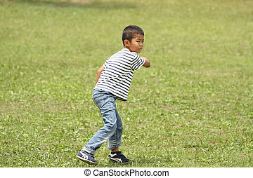 Japanese boy playing flying disc (first grade at elementary school)