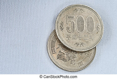 Five hundred Yen coins on japanese paper background. Macro image.