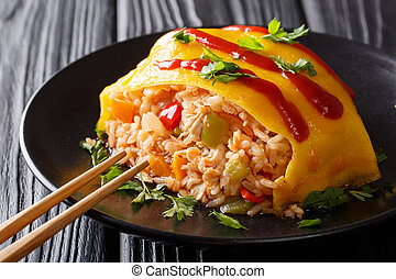 Japanese cuisine: omurice with rice, chicken and vegetables close-up. horizontal