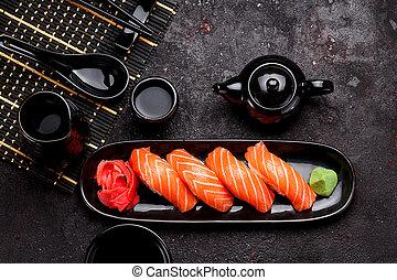 Japanese cuisine. Salmon sushi (nigiri) on a black plate and...