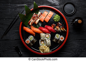 Japanese cuisine. Sushi set on a round plate over dark...