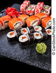 Japanese cuisine. Sushi with fresh ingredients on a black background.