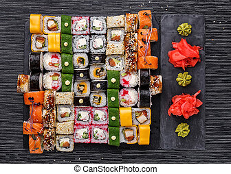 Japanese cuisine. Sushi with fresh ingredients on a black background. Different types of roles.