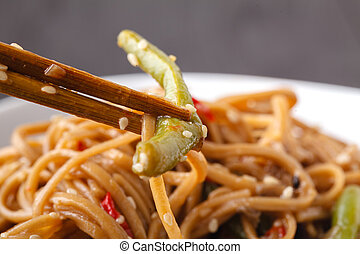Japanese famous foods. Yakisoba. Stir-fried noodles with chicken and vegetables. Closeup of chopsticks