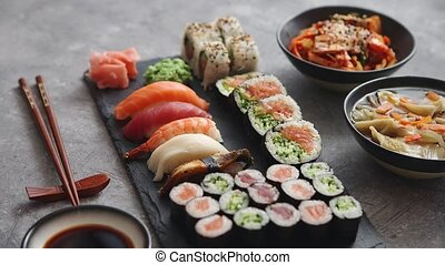 Various kinds of sushi placed on black stone board -...