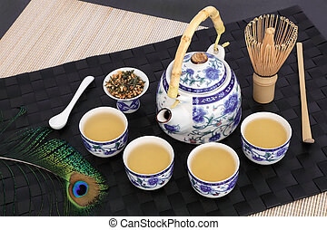 Japanese genmaicha fujiyama tea ceremony with oriental teapot, cups, whisk, stick stirrer, dried leaves and peacock feather on black mat, bamboo and slate background.