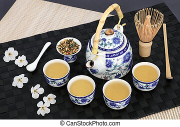 Japanese genmaicha fujiyama tea ceremony with oriental teapot, cups, whisk, stick stirrer, dried leaves and cherry blossom on black mat, bamboo and slate background.
