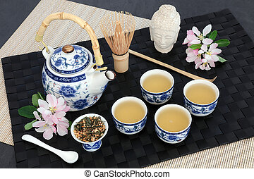 Japanese genmaicha fujiyama tea ceremony with oriental teapot, dried leaves, cups, whisk, scoop, Buddha head and spring blossom on black mat, bamboo and slate background.