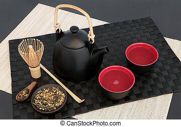Japanese genmaicha fujiyama tea with oriental teapot, cups, whisk, scoop and dried leaves on black mat, bamboo and slate background. Has many health benefits.