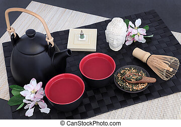 Japanese genmaicha fujiyama tea with oriental teapot, cups, whisk, dried leaves, Buddha statue, blossom and incense on black mat, bamboo and slate background.