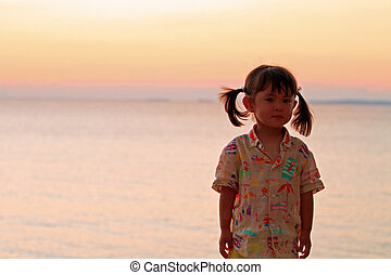 Japanese girl standing by the seaside in red (2 years old)