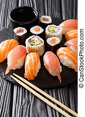 Japanese menu. Tasty set of sushi with salmon and tuna, California rolls, maki, soy sauce closeup. vertical