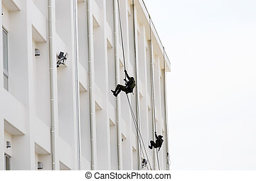 military men rappelling down the rope