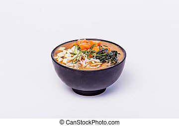 Japanese miso soup with tofu and salmon in a black bowl on a white background