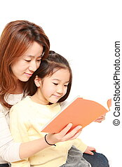 mother reading a book to her daugh