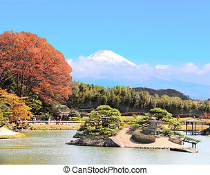 Japanese ornamental garden and sacred Mount Fuji (Fujiyama) in clouds on blue sky background, Japan