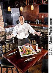 Japanese restaurant chef presenting sushi platter - Chef in...