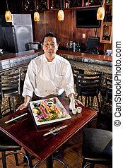 Japanese restaurant chef presenting sushi platter