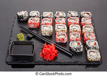 Japanese restaurant, sushi roll on black slate. Set for two with ginger and wasabi on a dark background.
