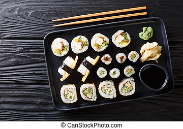 Japanese rolls set with tuna, tofu, eel, avocado, tamago closeup on a plate. Horizontal top view