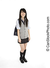 Portrait of a female Asian teenager dressed in the traditional Japanese schoolgirl clothing. Uniforms are worn by most of the female school children in Japan. She is standing on a white background and smiling.