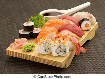 japanese seafood sushi and maki on wooden plate