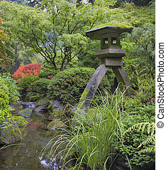 Japanese Stone Lantern in Garden with Rocks Trees Plants and Shrubs by Water Stream during Fall Season