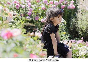 Japanese student girl sitting on the bench in rose garden (6 years old)