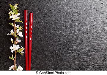 Japanese sushi chopsticks and sakura blossom on black stone ...