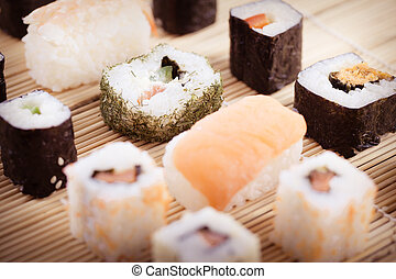 an assortment of different sushi pieces on a wooden bamboo sushi mat