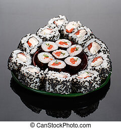 Japanese sushi food. Maki rolls and uramaki with tuna, salmon, caviar and cucumber. The roles are outlined in avocado form.