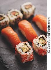 Japanese sushi on black stone plate