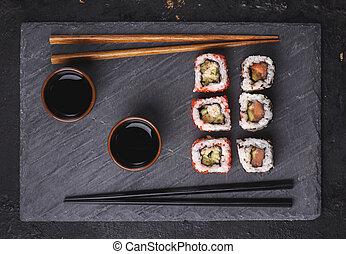 Japanese sushi rolls on black stone plate