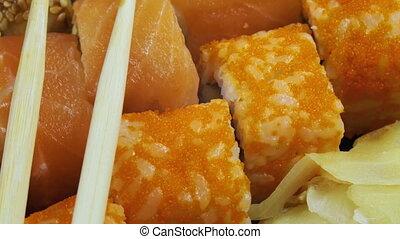 Japanese Sushi Rolls with Chopsticks Rotates. Close-up....
