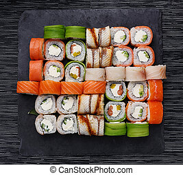 Japanese sushi set. Various types of roles on plate over stone background. Top view.