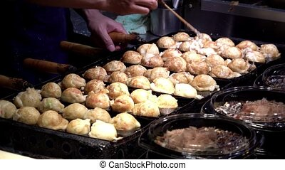 Slow Motion Japanese vendor prepare a ball-shaped Takoyaki on hot pan food in Osaka, Japan. Process to cooking the popular fried balls with octopus in local street food.