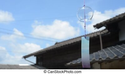 Japanese wind bell swaying in the wind in front of tiled ...