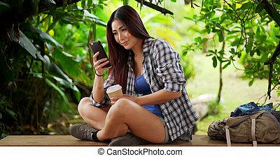 Japanese woman hiker taking a break on a nearby bench