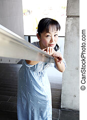 Japanese woman leaned on the stair railing